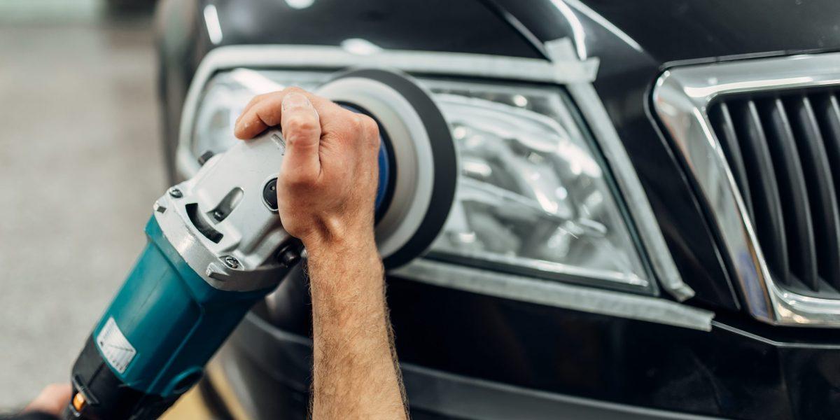 Auto detailing of car headlights on carwash service. Man works with polishing machine