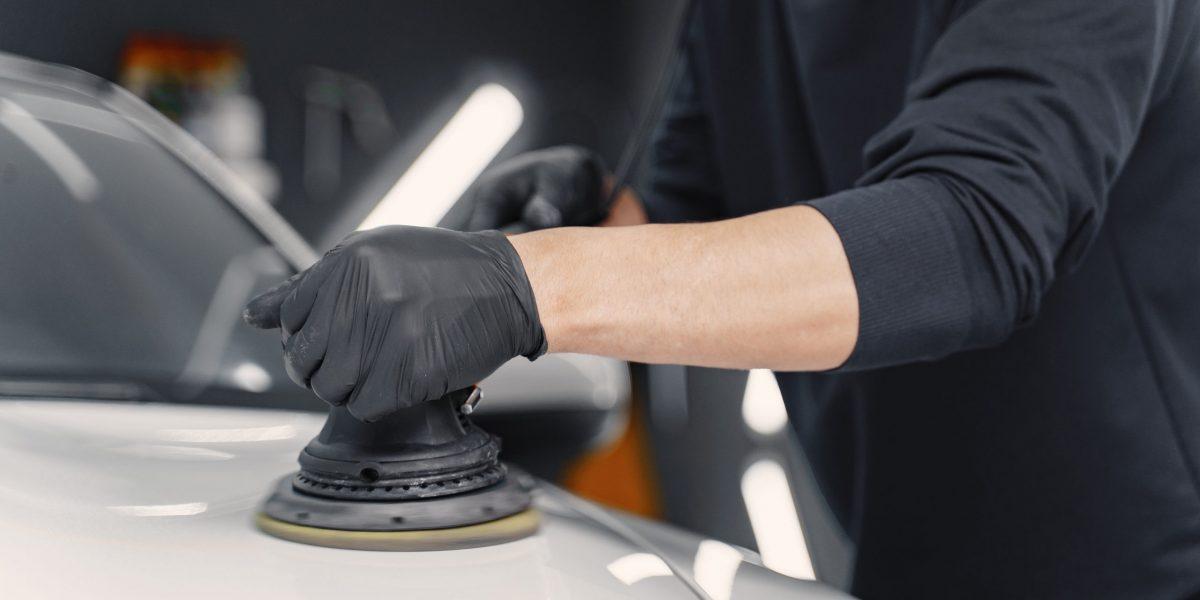Man in a garage. Worker polish a car. Man in a black uniform.