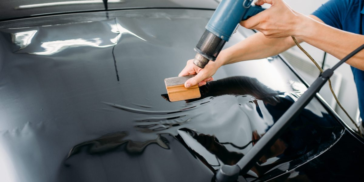 Male specialist with drier, car tinting film installation process, tinted auto glass installing procedure