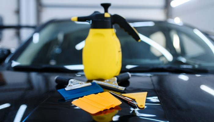 Tools for car tinting closeup, nobody, vehicle tuning service. Equipment for vinyl tint installation, business concept, tinted automobile glass