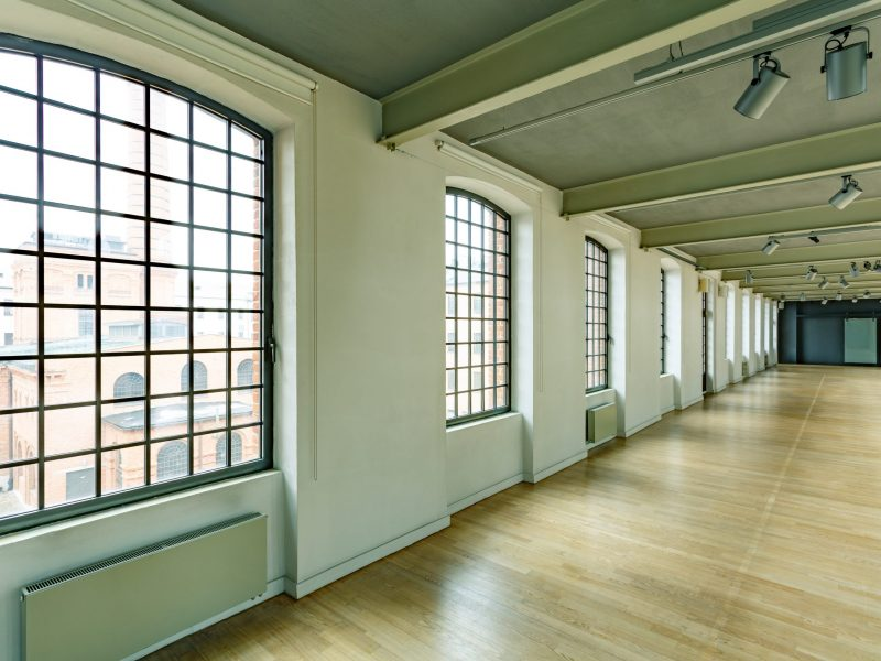 Industrial warehouse with windows, wood floor and modern lighting